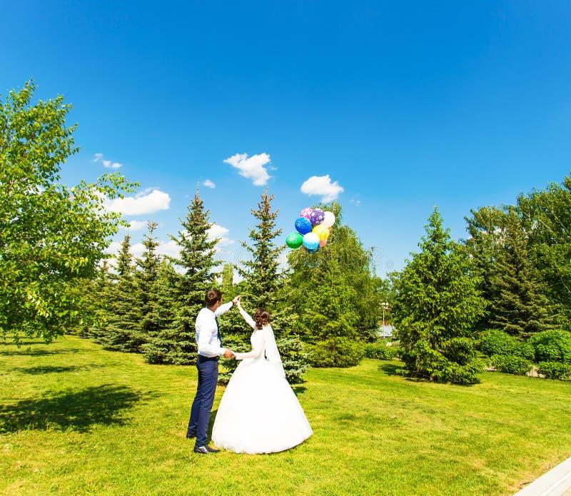 De bruid en de bruidegom kijken ballon in blauwe hemel royalty-vrije stock foto's