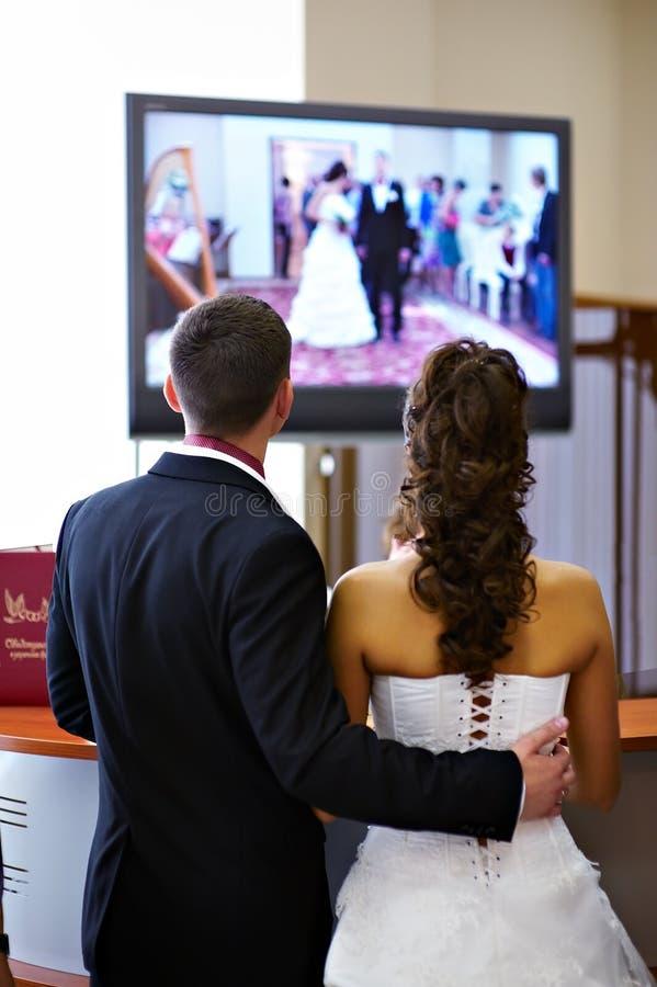 De bruid en de bruidegom letten op de video van zijn huwelijk royalty-vrije stock foto's
