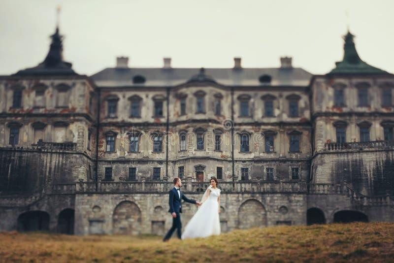 De bruid en de bruidegom lopen langs het gele gazon in de voorzijde van een ol stock afbeelding