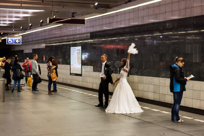 De bruid en de bruidegom nemen huwelijksfoto's in metro royalty-vrije stock foto