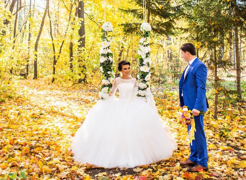 De bruid en de bruidegom op een schommeling in de herfstpark royalty-vrije stock afbeeldingen