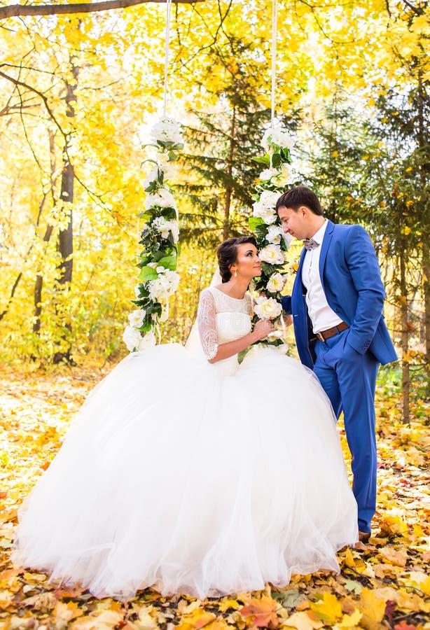 De bruid en de bruidegom op een schommeling in de herfstpark stock afbeelding
