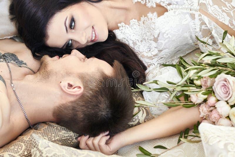 De bruid en de bruidegom worden klaar in de ochtend voor het huwelijk Houdend van paar die thuis koesteren Knappe bruidegom en ch stock afbeeldingen
