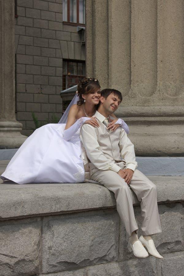 De bruid en de bruidegom zitten stock foto's