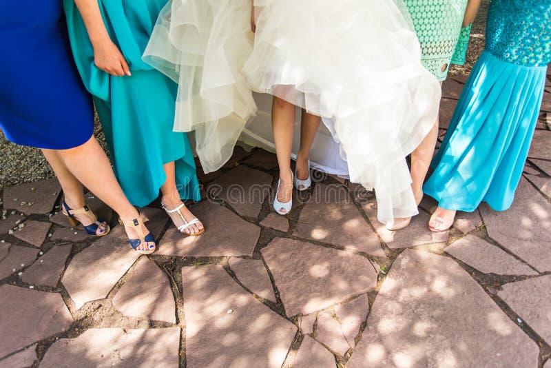 De bruid en de bruidsmeisjes pronken met hun schoenen bij huwelijk royalty-vrije stock foto