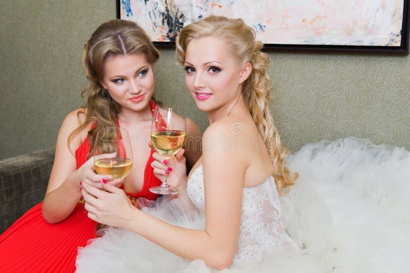 De bruid en haar bruidsmeisje met een glas wijn royalty-vrije stock foto