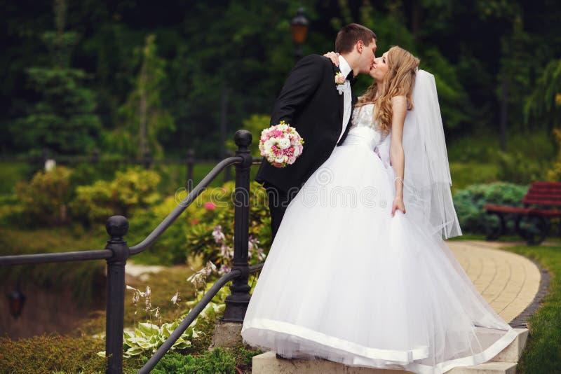 De bruid houdt de schouder van de bruidegom lopend met hem rond het park royalty-vrije stock afbeelding