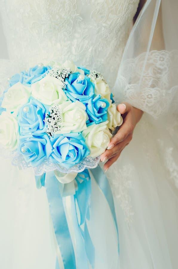 De bruid houdt een boeket van rozen Fragment van een witte huwelijkskleding royalty-vrije stock afbeeldingen