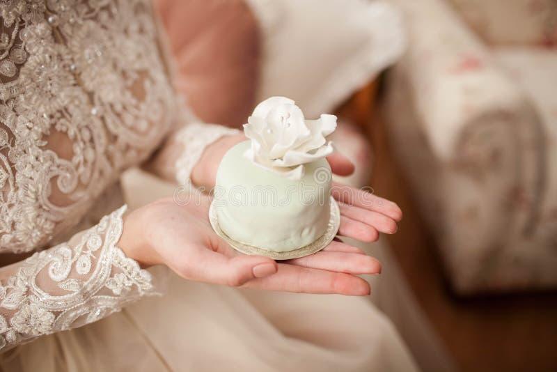 De bruid houdt een cake in handen stock afbeeldingen