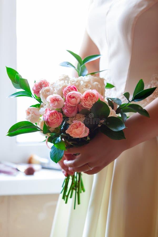 De bruid houdt een huwelijksboeket van witte en roze rozen royalty-vrije stock afbeelding