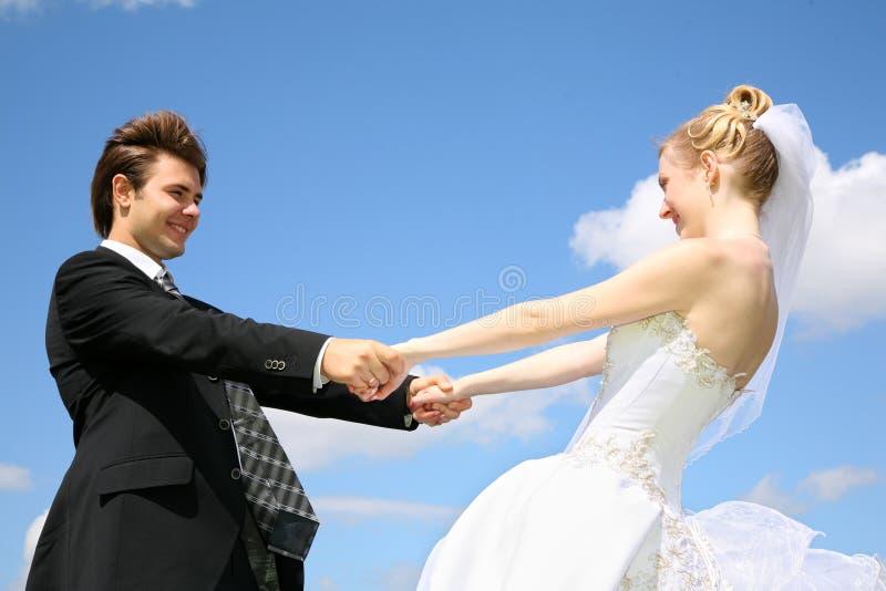 De bruid houdt fiance voor handen stock foto