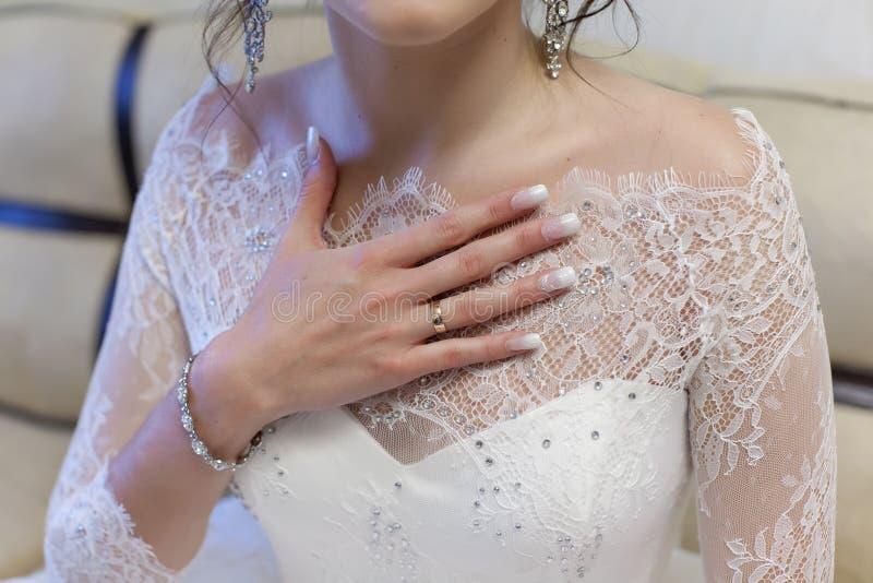 De bruid houdt haar hand met een verlovingsring op borst stock fotografie