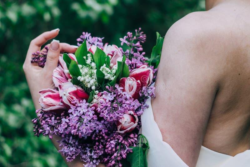 De bruid houdt in haar handen een roze en lilac huwelijksboeket van diverse bloemen stock foto