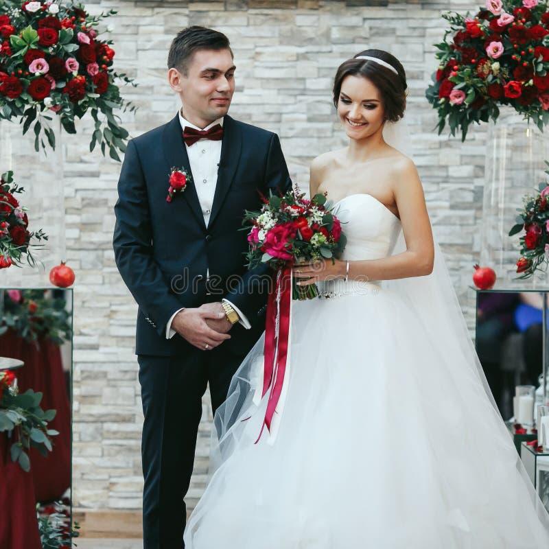 De bruid kijkt neer terwijl status met een fiance tijdens ceremon royalty-vrije stock foto's