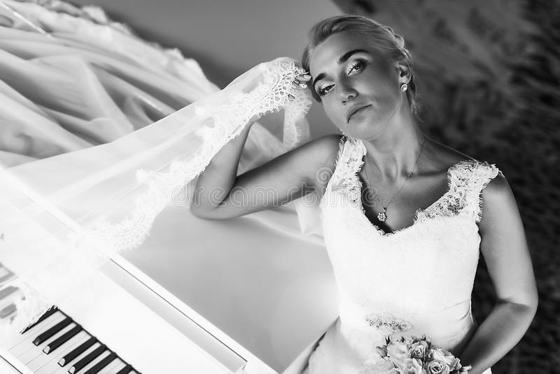 De bruid kijkt prachtige status achter een piano en het houden van haar hij stock foto