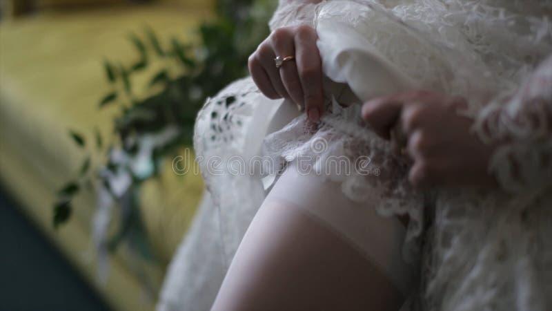 De bruid kleedt kousen op voeten Schoonheidsbruid in een kleding die kousenhuwelijk binnen dragen Vrouwelijke portret aardige dam royalty-vrije stock foto's