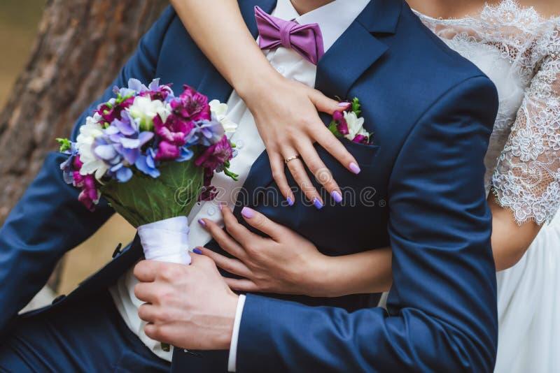 De bruid koestert de bruidegom een blauw purper boeket royalty-vrije stock afbeelding