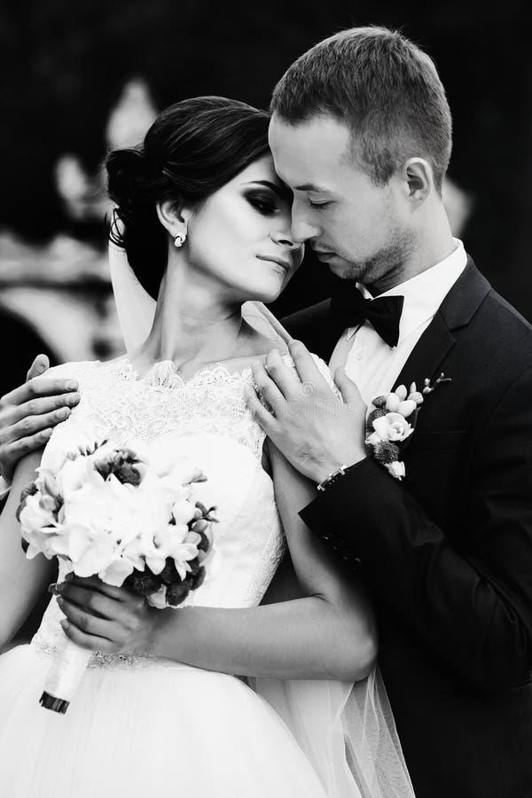 De bruid leunt aan bruidegom` s kin terwijl hij haar tedere schouders houdt stock foto's