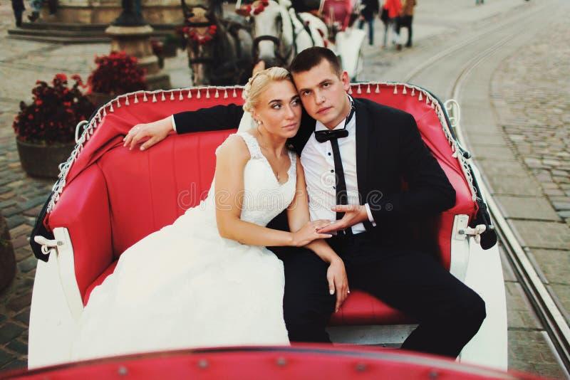 De bruid leunt aan de schouderzitting van de bruidegom in het vervoer stock afbeeldingen