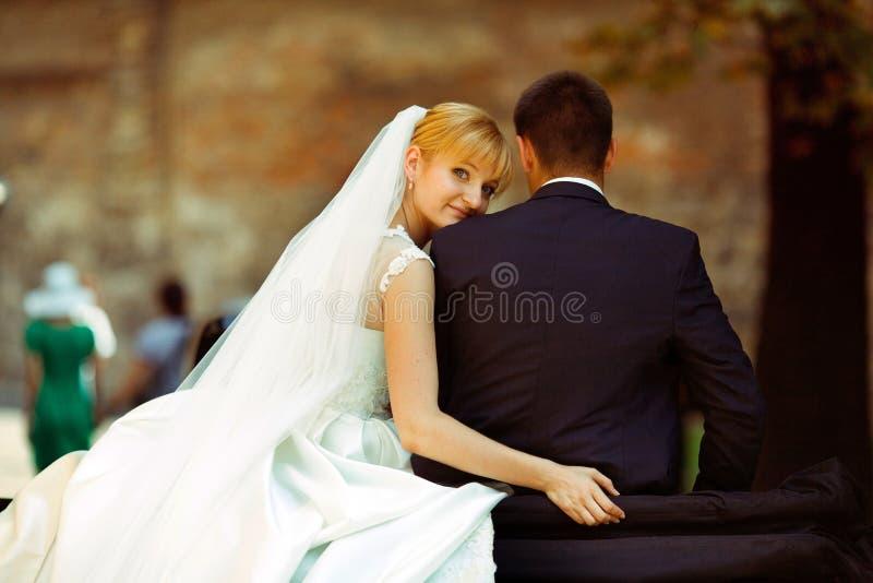 De bruid leunt aan de schouderzitting van de bruidegom met hem op een retro auto stock foto's