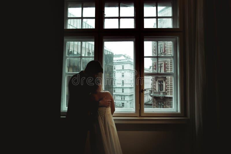 De bruid leunt aan een bruidegom die met hem door het venster Th bekijken royalty-vrije stock afbeelding