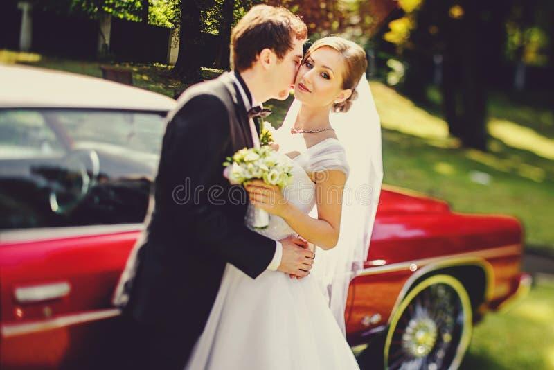 De bruid leunt op een bruidegom die zich op een drempel van een uitstekende auto bevinden stock foto