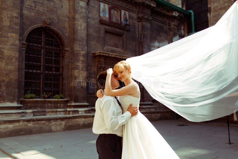 De bruid leunt teder aan het hoofd van de bruidegom terwijl de wind haar v wegblaast royalty-vrije stock afbeeldingen