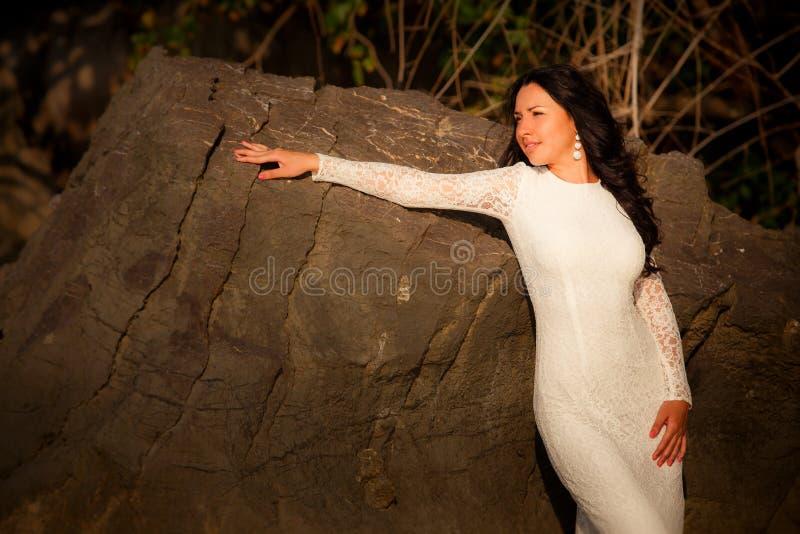 De bruid leunt tegen rots op strand stock foto's