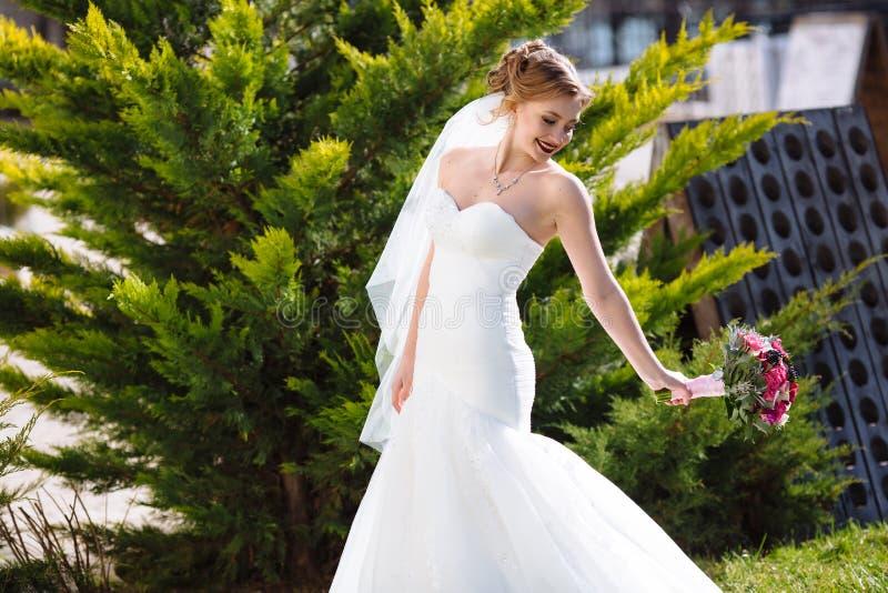 De bruid loopt in het park onder de sparren, heeft pret en speelt met haar huwelijksboeket Slank glimlachend meisje in een wit royalty-vrije stock afbeelding