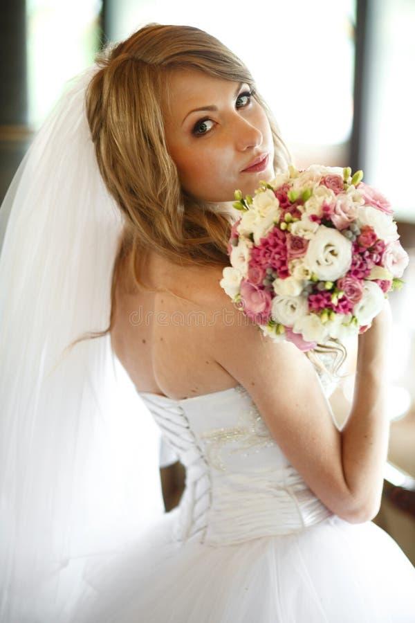 De bruid mengt haar haar en houdt huwelijksboeket in haar wapens stock fotografie