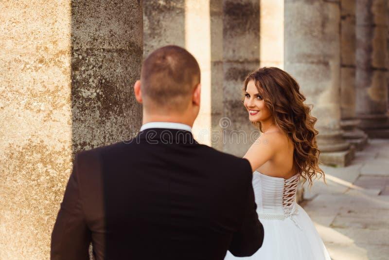 De bruid met donkere blondekrullen kijkt over haar schouder het glimlachen stock fotografie