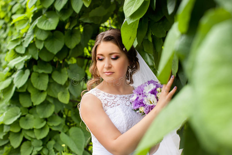 De bruid met een boeket van bloemen die in de foto op de aard stellen stock afbeeldingen