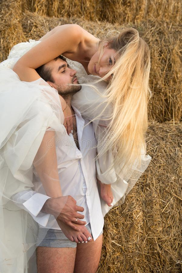 De bruid omhelst teder de bruidegom met hun voeten en leunt naar hem stock foto's