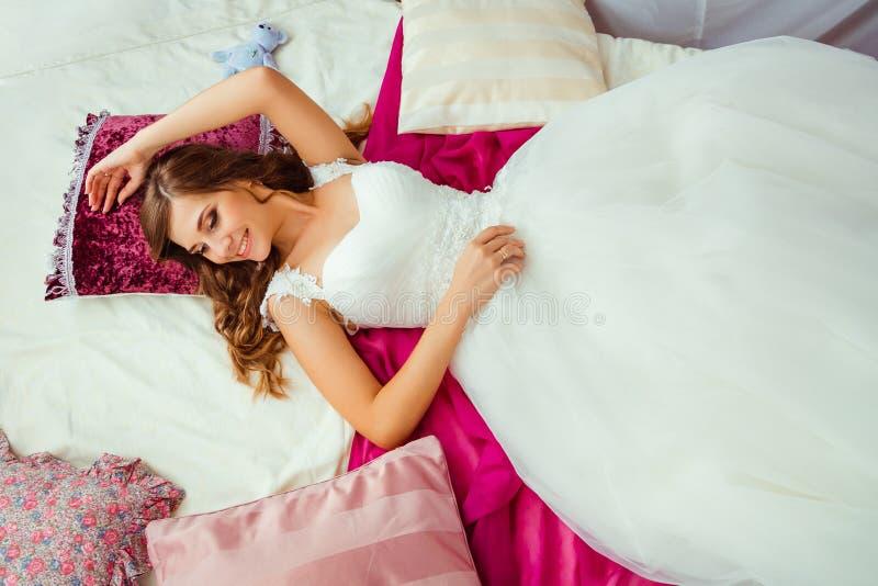 De bruid in prachtige kleding ligt op roze bed stock afbeelding