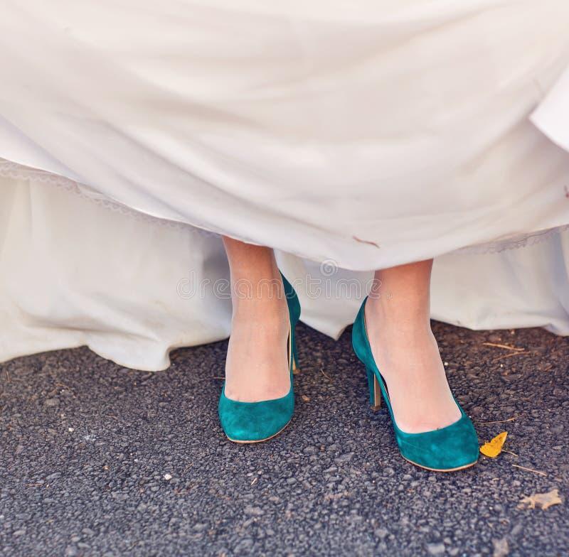 De bruid pronkt met haar turkooise schoenen bij huwelijk stock afbeeldingen