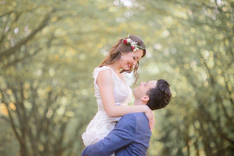 De bruid in rood omhult glimlachen aan een bruidegom terwijl hij haar tegenhoudt stock foto's