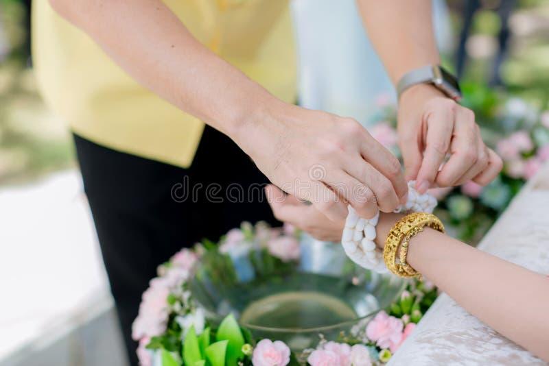 De bruid` s hand is gebonden met draad van de oudere cultuur in Thaise huwelijksceremonie bind heilige draad met indienen Thaise  royalty-vrije stock foto