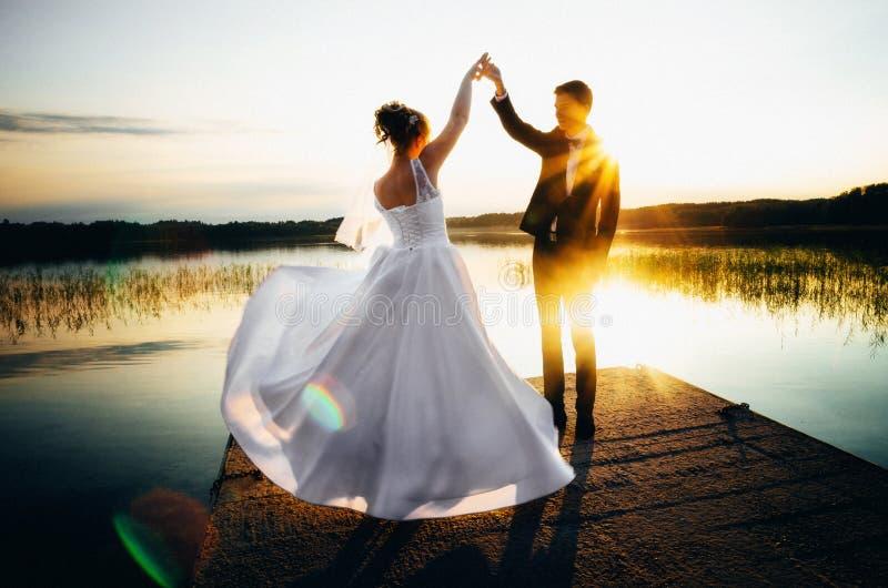 De bruid spint in een witte hand van de kledingsholding de bruidegom op de bank van het meer bij zonsondergang royalty-vrije stock foto's