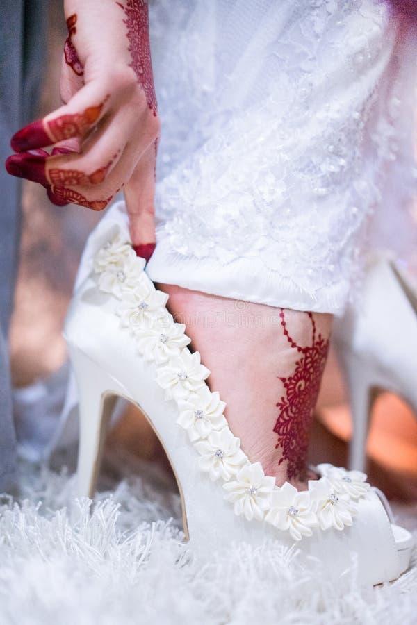 De bruid toont witte huwelijksschoenen royalty-vrije stock fotografie