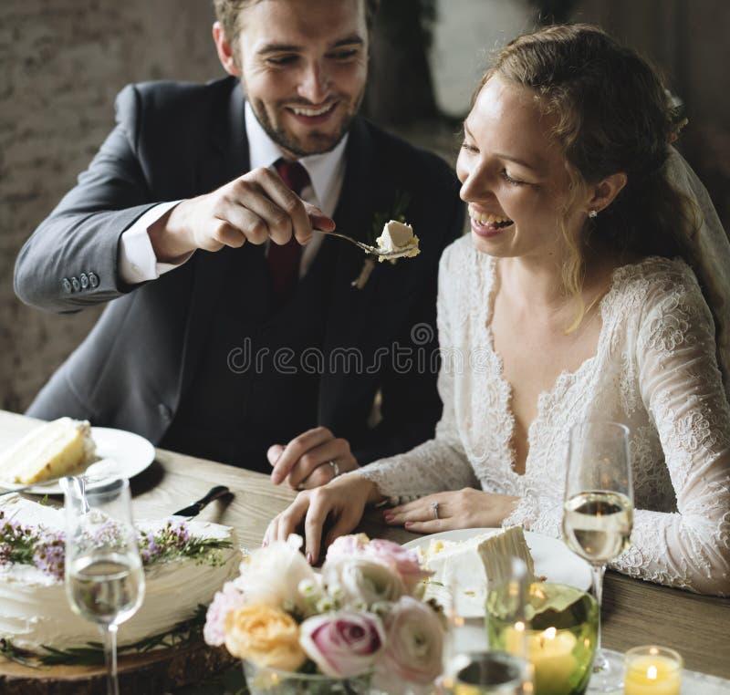 De Bruid van bruidegomfeeding cake to op Huwelijksontvangst stock fotografie
