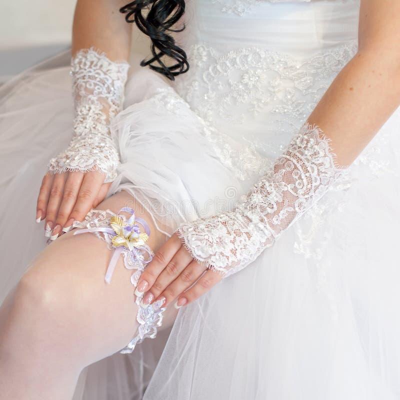 De bruid verbetert kouseband op haar been stock afbeeldingen