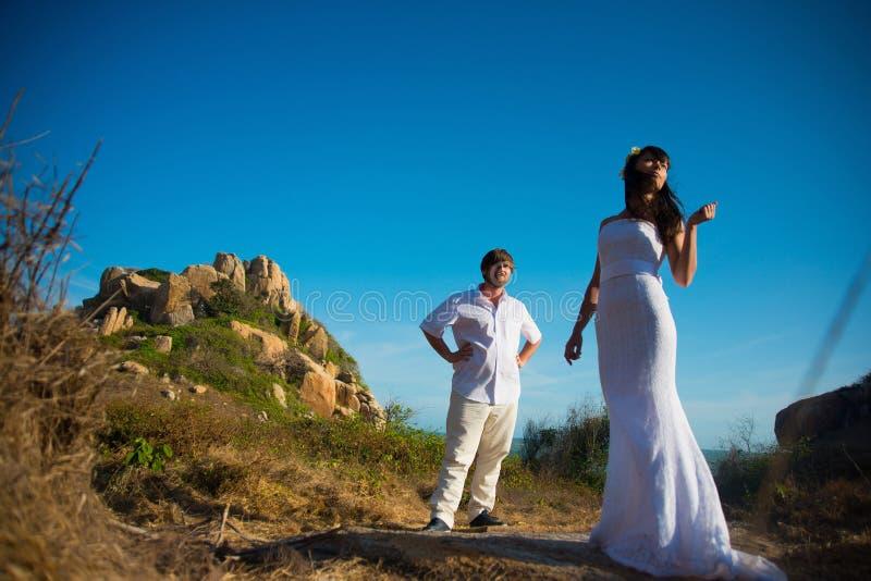 De bruid is in de voorgrond en de bruidegom is op de achtergrond in de bergen onder de blauwe hemel bij zonsondergang royalty-vrije stock foto's