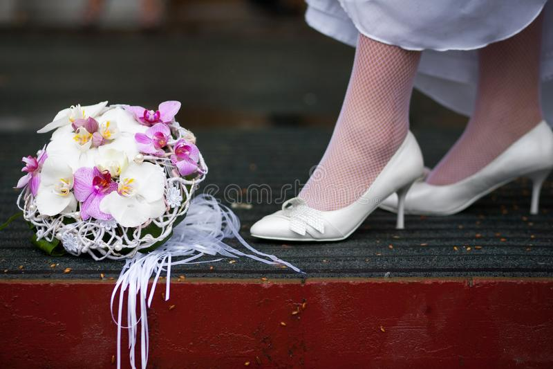 De bruid in witte huwelijksschoenen bevindt zich dichtbij het huwelijksboeket stock afbeeldingen