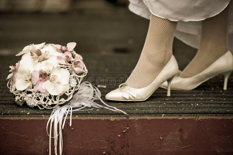 De bruid in witte huwelijksschoenen bevindt zich dichtbij het huwelijksboeket, uitstekende foto royalty-vrije stock fotografie