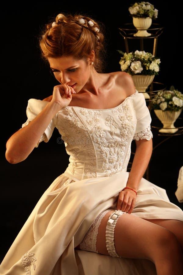 De bruid zet bruids kouseband vóór huwelijksceremonie royalty-vrije stock foto