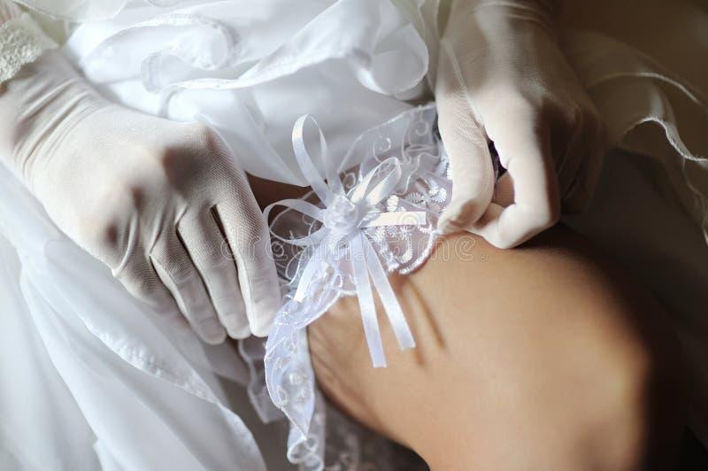 De bruid zet kouseband op een been royalty-vrije stock foto