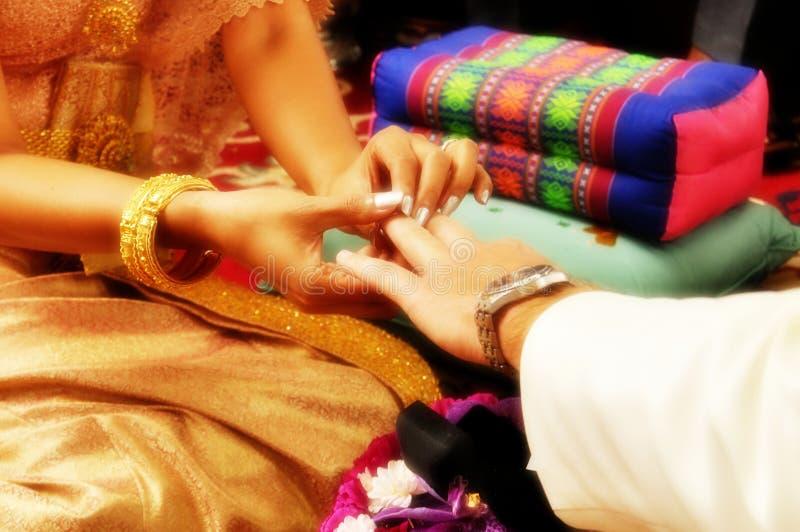 De bruid zet de ring op de bruidegom` s vinger tijdens een traditioneel Thais huwelijk royalty-vrije stock foto's
