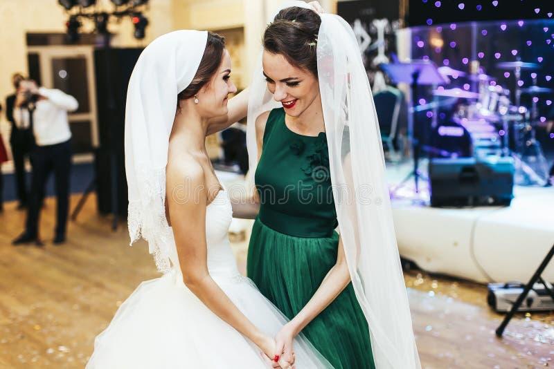 De bruid zet sluier op het bruidsmeisje stock fotografie