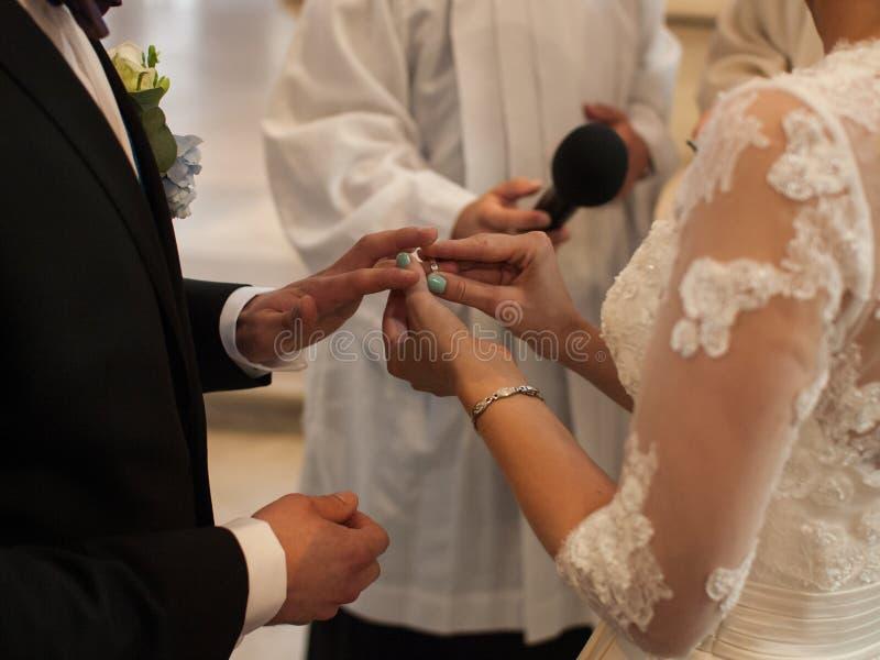 De bruid zet de trouwring op de bruidegom` s vinger tijdens de ceremonie in kerk onder de supervisie van de priester, Tsjechisch  royalty-vrije stock afbeelding
