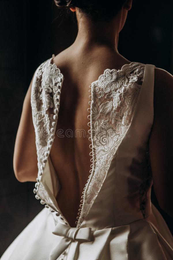 De bruid zet witte huwelijkskleding binnen ruimte stock afbeelding